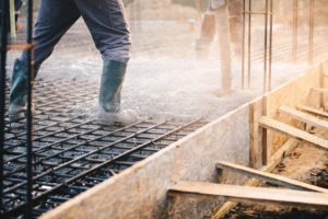 A construction worker prepares a grid of rebar for concrete