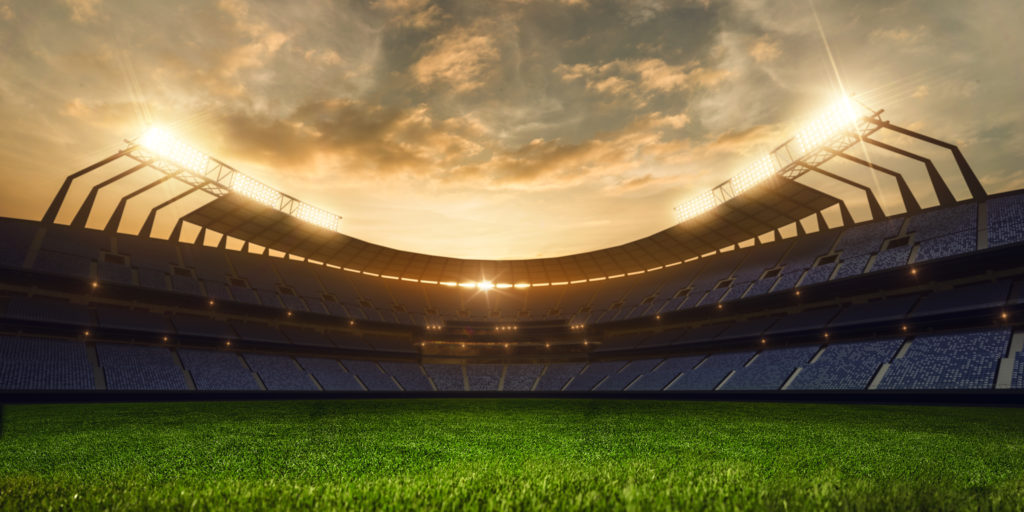 Empty baseball stadium with a clear and green field of grass with the sun setting in the horizon.