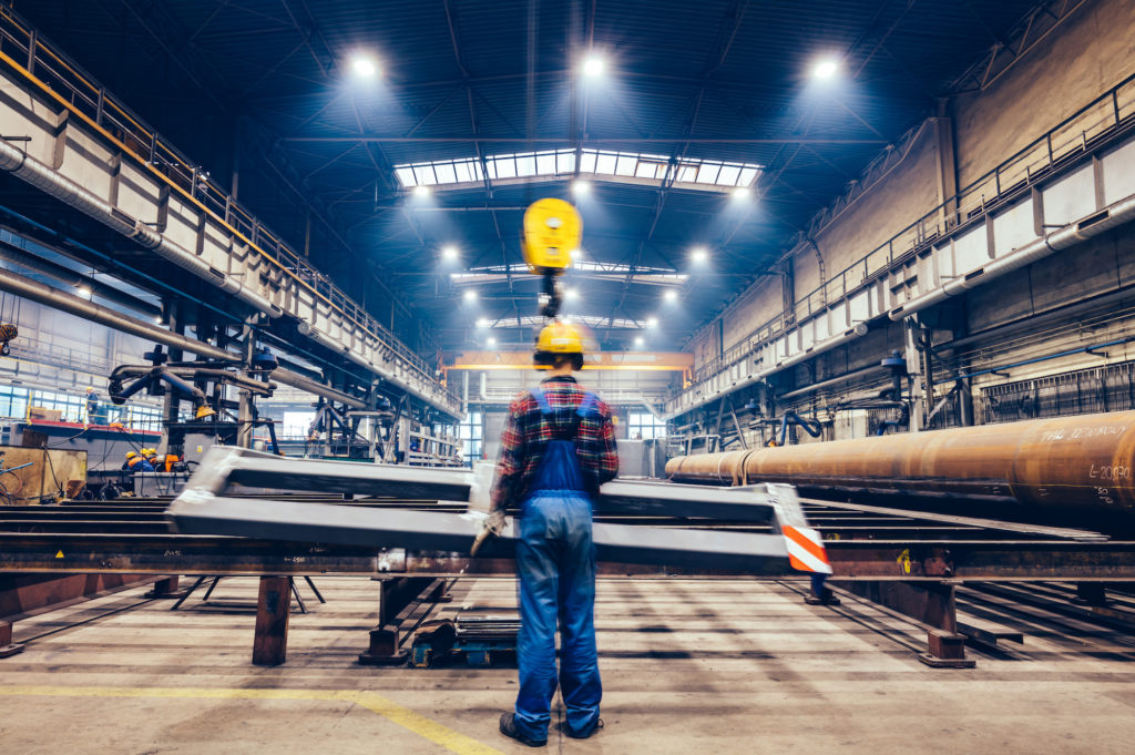 steel manufacturing plant with engineers wearing hardhats